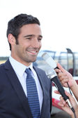 Man talking to reporters — Stock Photo