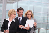 Business team looking at a laptop outside a glass building — Stock Photo