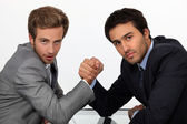 Two young men well dressed doing arm-wrest — Stock Photo