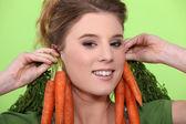 Kvinna som bär morötter som örhängen — Stockfoto