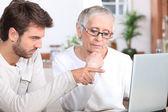 Jonge man toont een senior vrouw hoe om een laptop te gebruiken — Stockfoto