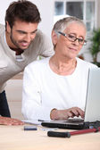 Man helping old lady with computer — Stock Photo