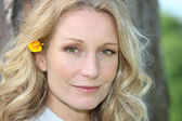 Blonde woman with flower in hair — Stock Photo