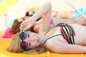 漂亮的女孩和她的朋友们躺在沙滩上 — 图库照片