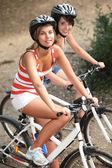 Portrait of 2 girls on bikes — Stock Photo