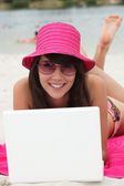 Jonge vrouw in een helder roze hoed met een laptopcomputer op het strand — Stockfoto