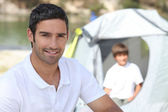 Father and son camping by river — Stock Photo