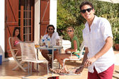 Genç adam bir açık hava grill'de yemek — Stok fotoğraf