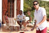 Ung man matlagning på en utomhus grill — Stockfoto