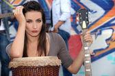 Музыкант, опираясь на барабане и проведение гитара — Стоковое фото