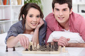 Young man and young woman playing chess — Stock Photo