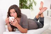 Woman drinking coffee on the sofa — Stock Photo