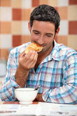 Smiling man eating croissant for breakfast with a magazine — Stock Photo