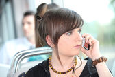 Trendy young woman using her cellphone on a tram — Stock Photo