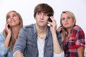 Three teenager using mobile telephones — Stock Photo