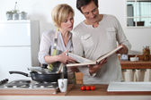 Couple cooking together with a recipe book — Stock Photo