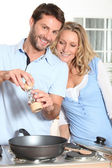 Couple using peppper grinder while cooking in the kitchen — Stock Photo