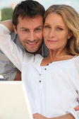Couple with laptop in garden — Stock Photo