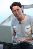 Man working at laptop computer by the sea — Stock Photo