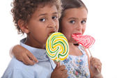 Couple of children with lollypops — Stock Photo