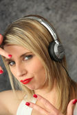 Woman wearing headphones making youthful gesture — Stock Photo