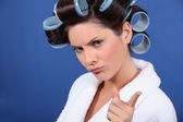 Bad tempered woman with curlers in her hair — Stock Photo