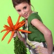 Stock Photo: Pretty girl holding carrots on green background