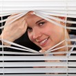 Woman looking through the blinds — Stock Photo