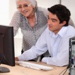 Old lady and young man sat by computer — Stock Photo