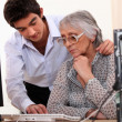 Young man showing elderly lady how to use computer — Stock Photo