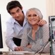 Young man helping an elderly lady use a computer — Stock Photo #7790825