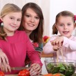 Mother and her two girls making a salad — Stock Photo