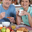 Smiling couple at breakfast — Stock Photo