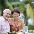 Older couple eating outdoors — Stock Photo