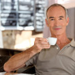 Stock Photo: Elderly mhaving espresso on terrace