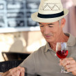 Elderly man drinking a glass of rose in a cafe - Stockfoto