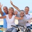 Happy foursome gone for a ride by oceanfront — Stock Photo
