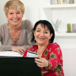 Mature women using a credit card online — Stock Photo