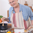 Elderly woman cooking with the help of a recipe - Stock Photo