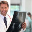 Happy doctor looking at x-ray image of hand — Stock Photo