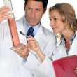 Doctor and nurse holding tube — Stock Photo