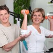 Stock Photo: Wombeing helped by her personal trainer