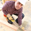 Stock Photo: Builder sawing wood