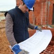 Builder examining plans — Stock Photo