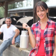 Stock Photo: Woman with a churn of milk in front of a herd of cows