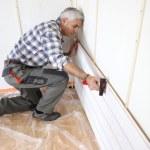 Man putting up interior wood cladding — Stock Photo #7793288