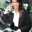 Stock Photo: Businesswomsmiling on phone in car