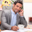 Man taking a business call over breakfast — Stock Photo
