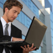 Young executive using a laptop outside an office building — Stock Photo