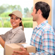 Man receiving package from a delivery girl — Stockfoto